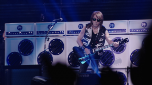 Tak performing with his latest signature instrument styled after the Gibson Firebird.